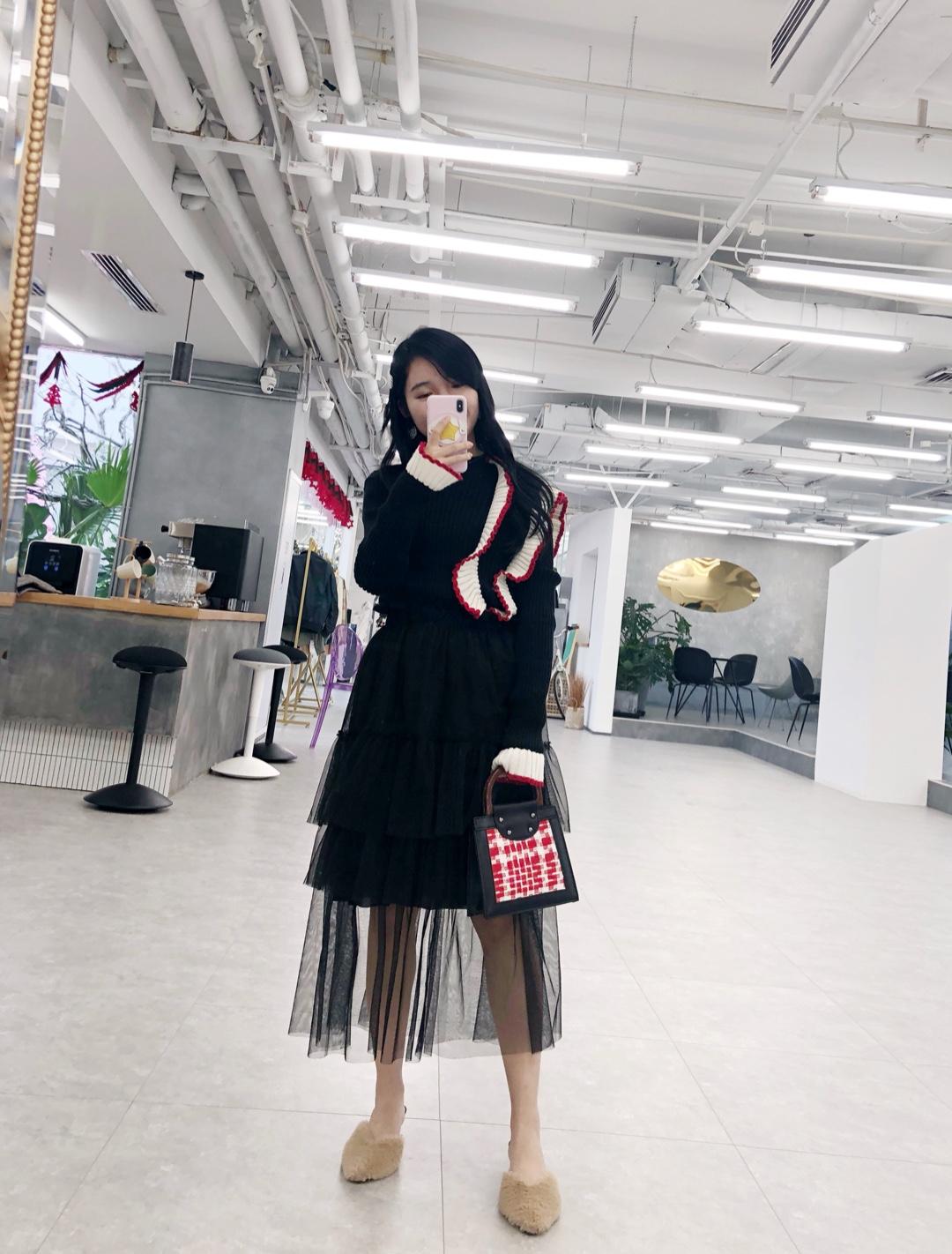 这件黑色毛衣不仅用到了我喜欢的荷叶边元素,还加入了撞色的元素🌟。 整体的黑色调为了突出它的独特性,在立体荷叶边上采用了黑-白-红的撞色,产生了强烈的时尚视觉效果~荷叶边有少女的style,那下半身也选择了仙气十足的纱裙💕。 #少女感赛高,过年就靠它取胜了# 👜包包:KITAYAMA北山制包所 包的配色恰巧和衣服相呼应~