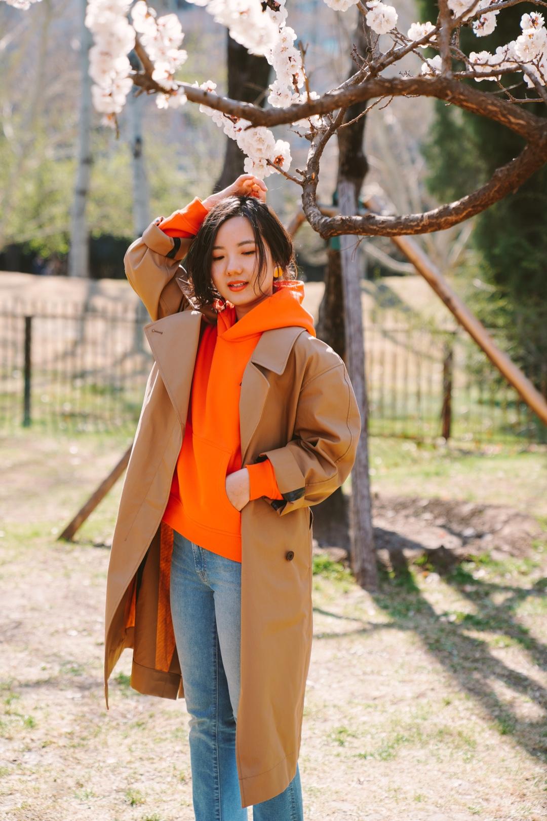 小毛穿搭| 风衣的一周穿搭——帽衫搭配 🧥在短暂珍贵的风衣季里安排了一周风衣穿搭计划,第一套就选择最轻松舒服的穿法吧~  经典款深卡其色风衣内搭颜色鲜亮的橙色帽衫,袖口处也露出卫衣的颜色,让严肃的风衣有了春日的活泼。  浅蓝色牛仔裤和小白鞋也是不失时尚的休闲百搭单品。 #好天气,就该穿得美美出去踏春!#