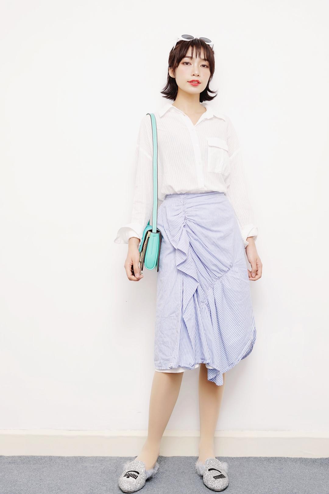 #马卡龙色开启霸屏模式!#  今天给大家推荐一套超级清爽的穿搭,白色衬衫简约清爽,松开两颗纽扣露出锁骨,不经意间透出小性感,搭配今年春夏流行元素之一的不规则褶皱衬衫裙,很好修身腿部,开叉设计,微微露腿,又是一处加分的性感,清爽的蓝色条纹,简直让闷热的初夏生出丝丝凉意,搭配蒂芙尼蓝的包包,更加活泼,银色亮片鞋上有淡蓝色的毛毛和裙子相呼应,显白又清爽~