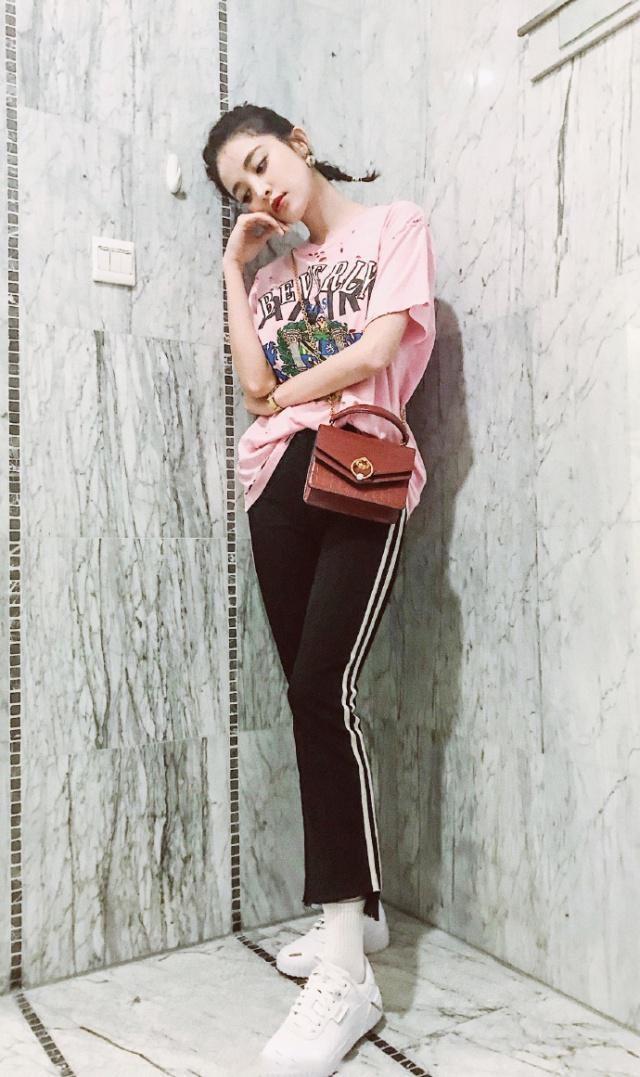 古力娜扎这一套穿搭甜美可爱,满满的学院风格。上身是一件粉色的T恤,上有字母印花和非常时髦的图案,在加上一些不规则洞洞剪裁点缀,透露出了一股满满的青春活力气息,搭配这条黑色的修身裤,裤子是高腰的设计,高腰的设计大家也都懂,极其显腿长,九分裤的长度和裤脚的不规则设计,清新又显时髦感,裤边两条白色的纹路设计,经典的黑白搭配简约又好看。#沉闷雨季,明亮色穿搭拯救心情!#
