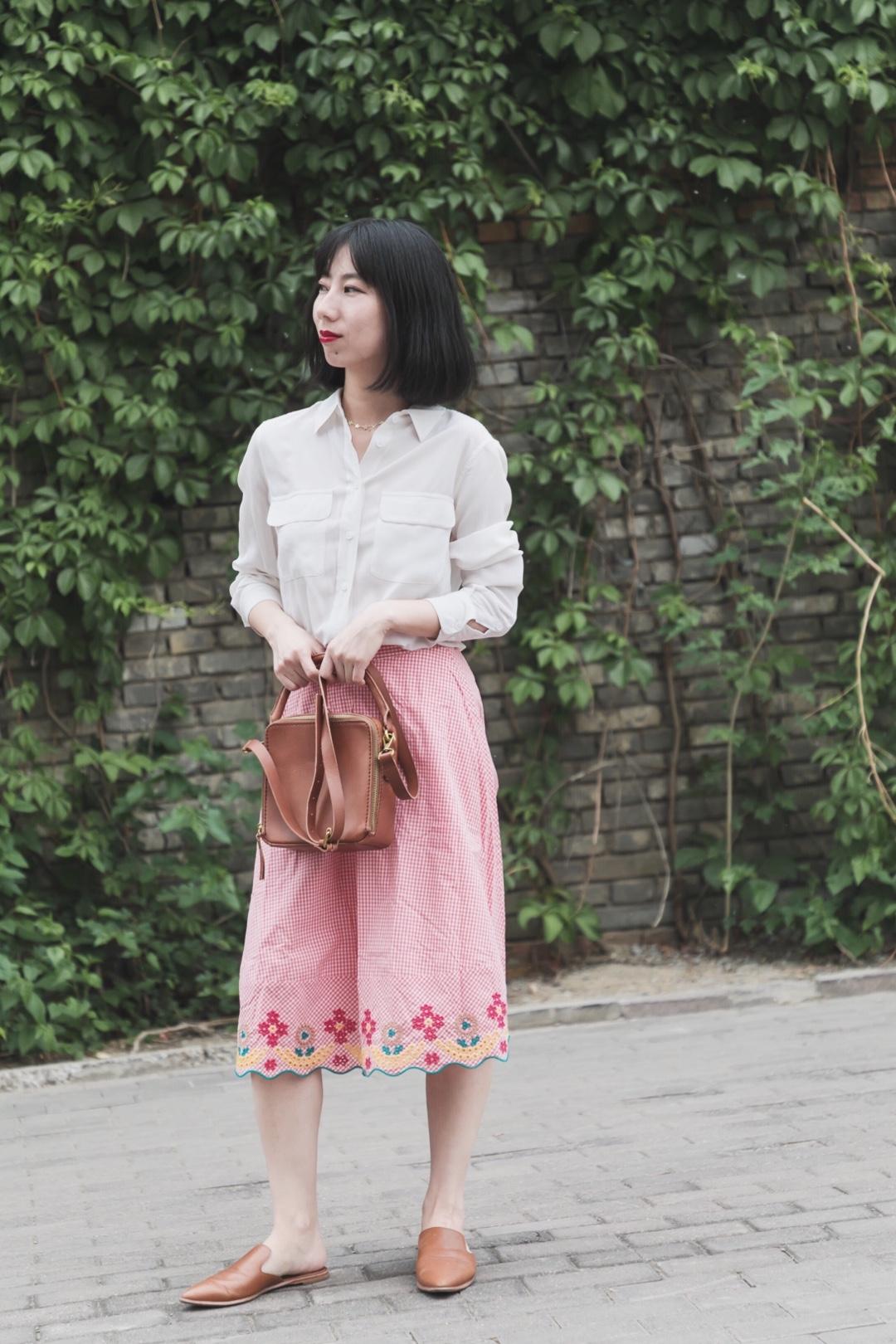 #夏日显白穿搭最全攻略#  衬衫和长裙的夏季搭配: 🌸真丝白衬衫搭配粉色长裙,白色和粉色的搭配是很适合夏季的温柔搭配,比较显得肤色白,仙女长裙没错了~裙子设计是高腰和刺绣设计,细节丰富。 配饰是一只比较复古的方形盒子,搭了同色穆勒拖鞋,平衡一些少女感,添加一些酷酷的赶脚。