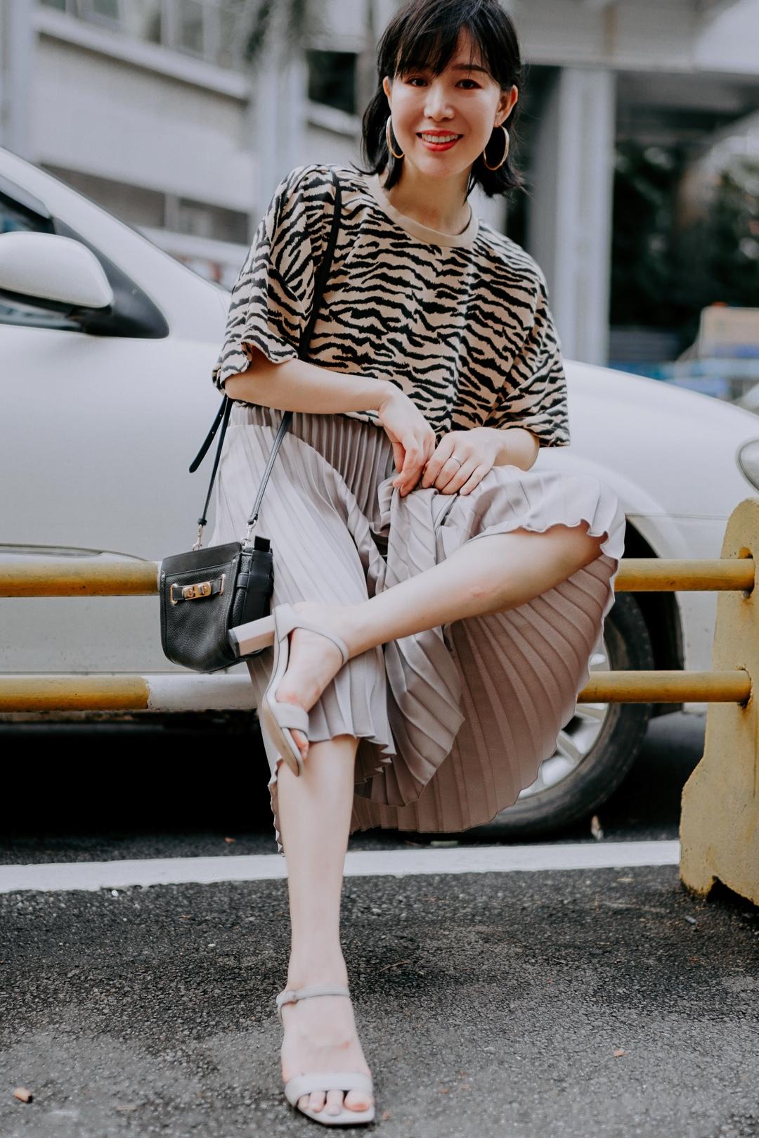 虎皮纹这样穿也可以上班 上身是虎皮纹的休闲T,感觉很潮的样子,下半身混搭了非常优雅的灰色百褶裙,让动物纹也没那么野性了,长长的百褶裙,也显得腿很修长,搭配裸灰色的百搭高跟鞋,拿上简约黑色的包包,一对金色大圈圈耳环,你就是办公室最靓的那个丫  #上短下长,腿长一米八!#