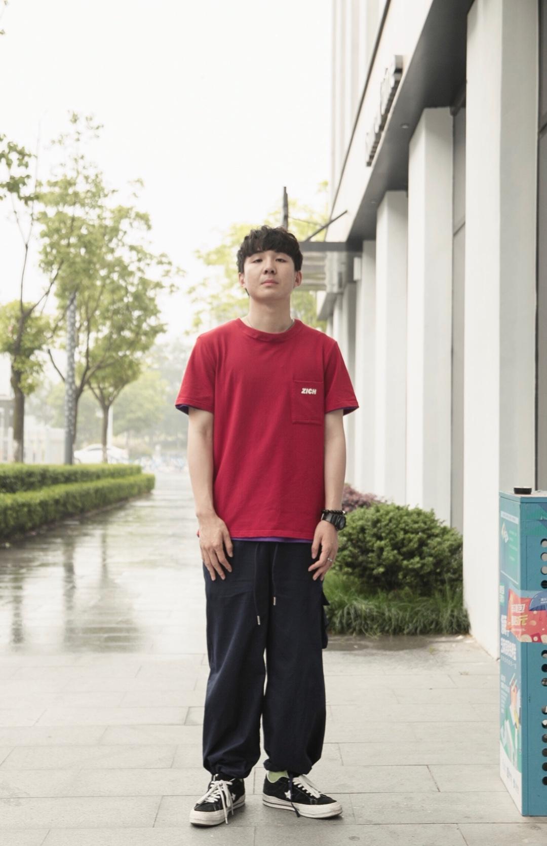 #毕业旅行穿搭,你还缺这套look!# 大红色的T恤上身非常显白,简单的印花让衣服看起来很适合男生,亮点是背后的印花,搭配藏青色的束腿裤,简直十分的帅气呀!