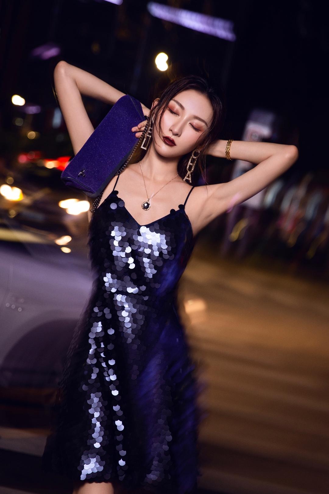 OOTD|暂时逃离工作吧!时髦女孩的派对穿搭 最近创作了两组不同风格的都市时髦女孩的party穿搭 LOOK,都是晚上在市区路边拍的。我相信有趣有品味的时髦女孩本身应该是多样化的。 这组是紫色复古神秘风,紫色吊带亮片裙在夜晚的路边光线下特别好看。搭配紫色细闪包包跟凉鞋。深圳当晚下着细雨,天气潮湿刚卷好的头发瞬间没了型,索性把头发打湿,搭上深色口红更有气场。 介绍下搭配的单品: 连衣裙:CHENG CHENG-OFFICIAL是我非常喜欢的新晋小众轻奢设计师品牌,风格就是可盐可甜,复古浪漫风跟现代艺术感融合得很好,不失女人味又有品位,接下来会持续关注。 包包:Vivienne Westwood 这个蓝紫色包包是很久前在HK入手的,不是新款,但就是一眼相中,颜色非常特别,细闪的质感又不是大亮片。好看又低调很适合当晚宴包。 耳饰:CHANEL 今年大火的字母耳环,此款一出好多品牌跟风,不用我多介绍啦,是我最近的新宠。 鞋:Lost in echo 把鞋做得跟艺术品一样美。 #肉系少女最爱,显瘦度满分!#