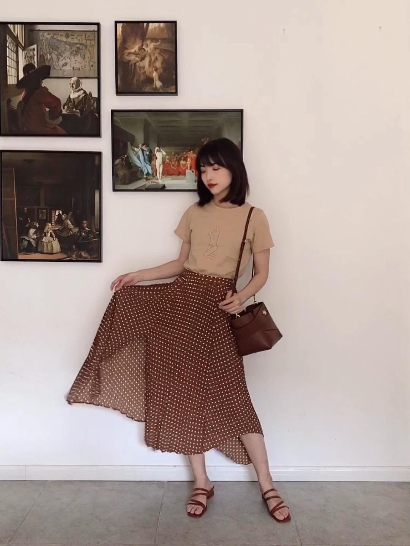 【Valerie's OOTD】Vol.267 这一套穿搭的主色调是奶茶色+棕色,超级温柔而且不挑人的颜色。 上衣是一件超甜的T恤,上面的印花是一个很好看的人体线条,颜色像奶茶一样甜。下装是一条高腰A字裙,小百褶的设计不会显老气,棕色波点也很复古,A字裙非常遮肉,而这种上短下长的搭配方法又很显高。 再搭配一个棕色系的包包和线条凉鞋,整套穿搭干干净净,超适合约会了。 #别慌!肉肉急救穿搭术来啦!#