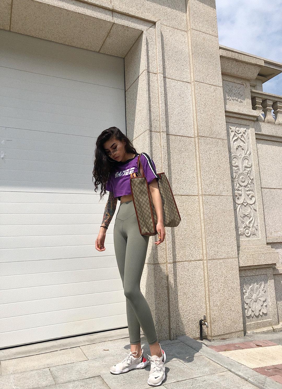 #网红款懒人套装,疯狂种草!# 这条legging 可厉害了 颜色超级正 是那种 绿的很高级的颜色 这个颜色看起来就很贵 上衣我选了一件紫色的短上衣 充分的展现了腿的比例 更大幅度的拉长了身材比例 特意背了一个大包 要不然感觉太空荡 服装太单调 配饰要来凑