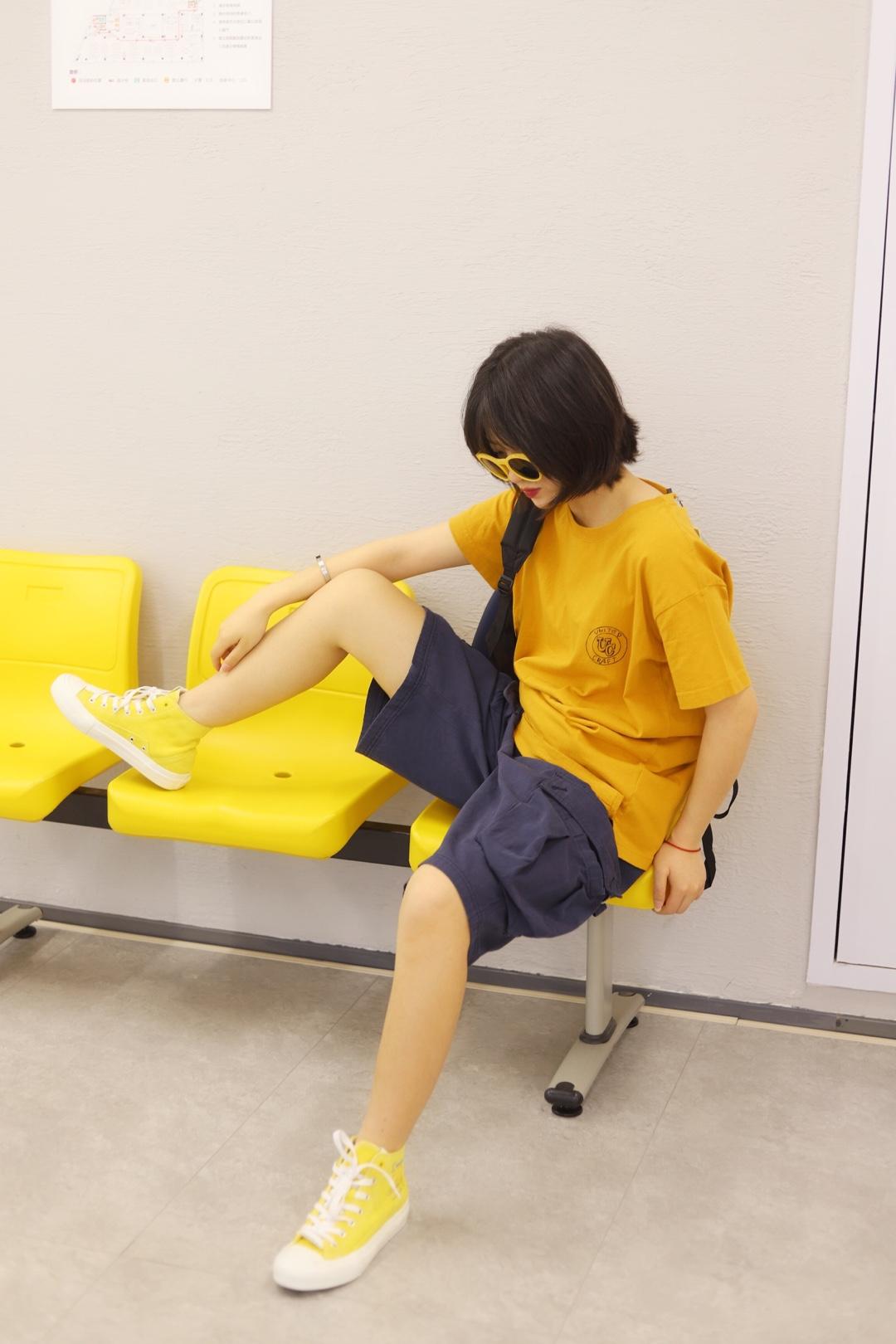 上身是一件黄色印花短袖 下身是一条藏青色工装中裤 搭配一双黄色高帮帆布鞋 戴上一顶黄色的墨镜 背上一个黑色的包包 这样一身就简单能够快速出门还很显瘦啦 #懒癌+肥胖?终于有救了!#
