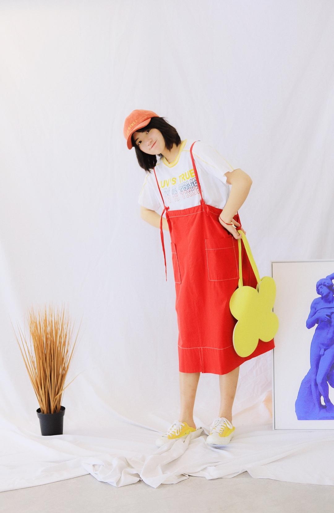 上身是一件白色黄领印花短袖 搭配一条红色撞色明线大口袋半身裙背带裙 穿上一双黄色帆布鞋 戴上一顶橙色的鸭舌帽 拎上一个黄色的蝴蝶包 这样一身颜色就超级好看啦 饱和度比较高很适合夏天呢 #鬼马少女元气穿衣经#