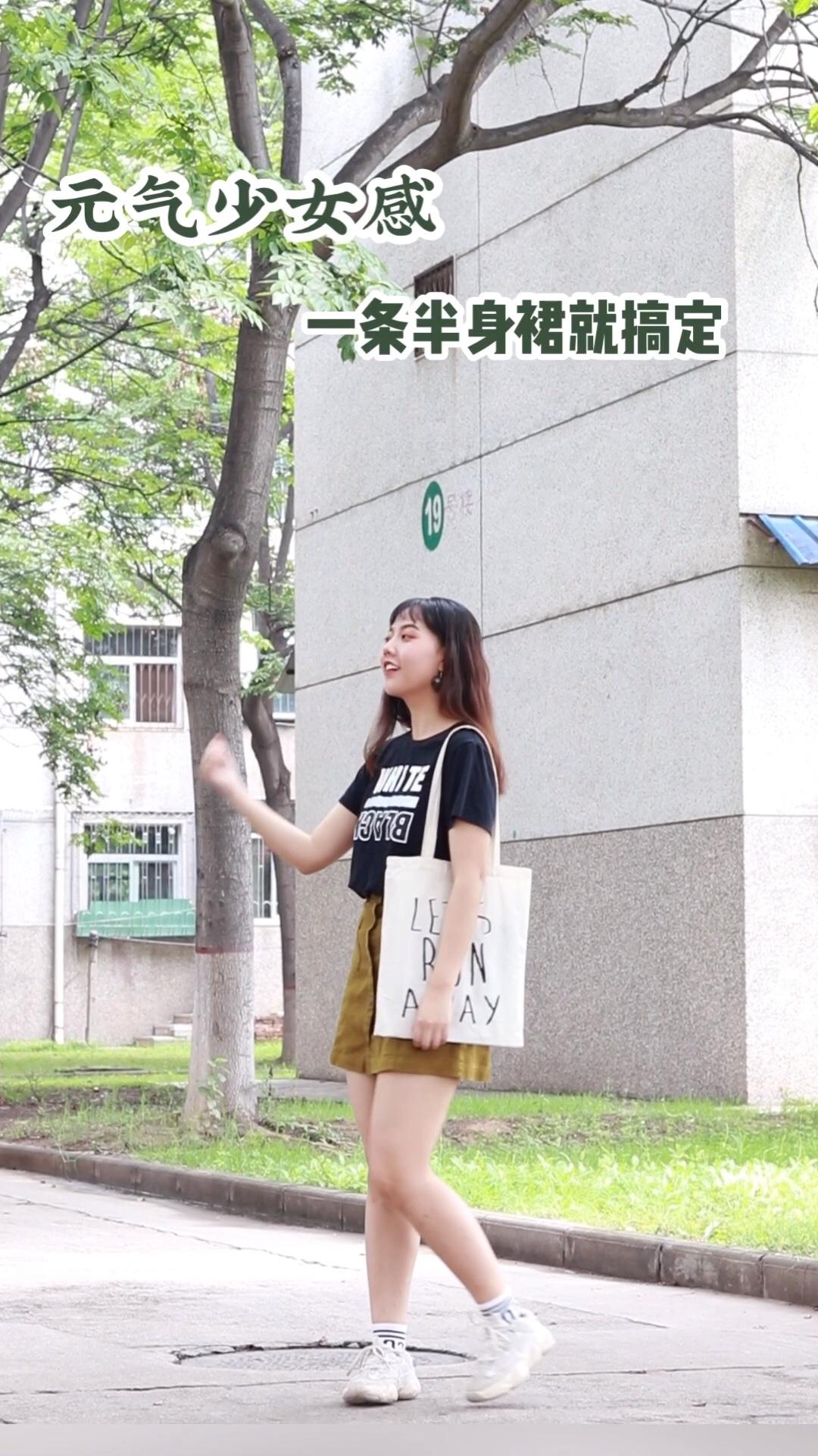 #T恤搭半裙的100种穿法# 上衣是一件黑色的白色印花T恤 版型宽松 短款设计 下身是一条果绿色的牛仔半身裙 高腰设计 矮妹子也不用担心 而且一点也不会显胯宽 非常适合梨形身材的女孩