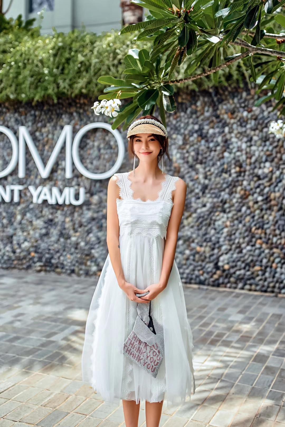 蕾丝秀吊带连衣裙 吊带是对称型的花边蕾丝绣,拓宽了原本的线条感,覆在肩处更有魅力。裙身是更为紧致的长织带形蕾丝绣,层层的叠加让白色不再单调。裙摆则是纱裙之上融入几条蕾丝绣条,明暗有致虚实交合,纯白色的裙子上身反而有了饱满的效果。  