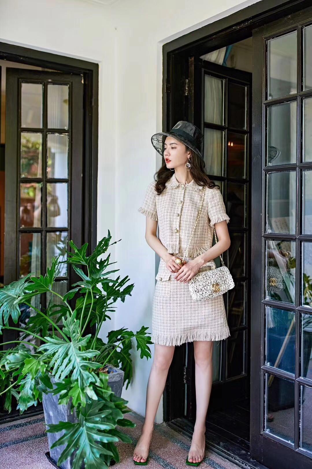 绒丝格纹套装 米色系的浅色格纹,会更适合于夏天。当然格纹也不局限于常见的单品,裙装套装遇见格纹,多了一丝复古女王气质。上衣是衬衣式的单翻领,纽扣点缀门襟。袖边以及做短的衣尾都拼入了绒毛丝的坠子,亲肤又撩人。下身的半裙,呼应衣服设有纽扣翻盖口袋,层次感更强。绒边的裙摆迎着风,也更有韵味。