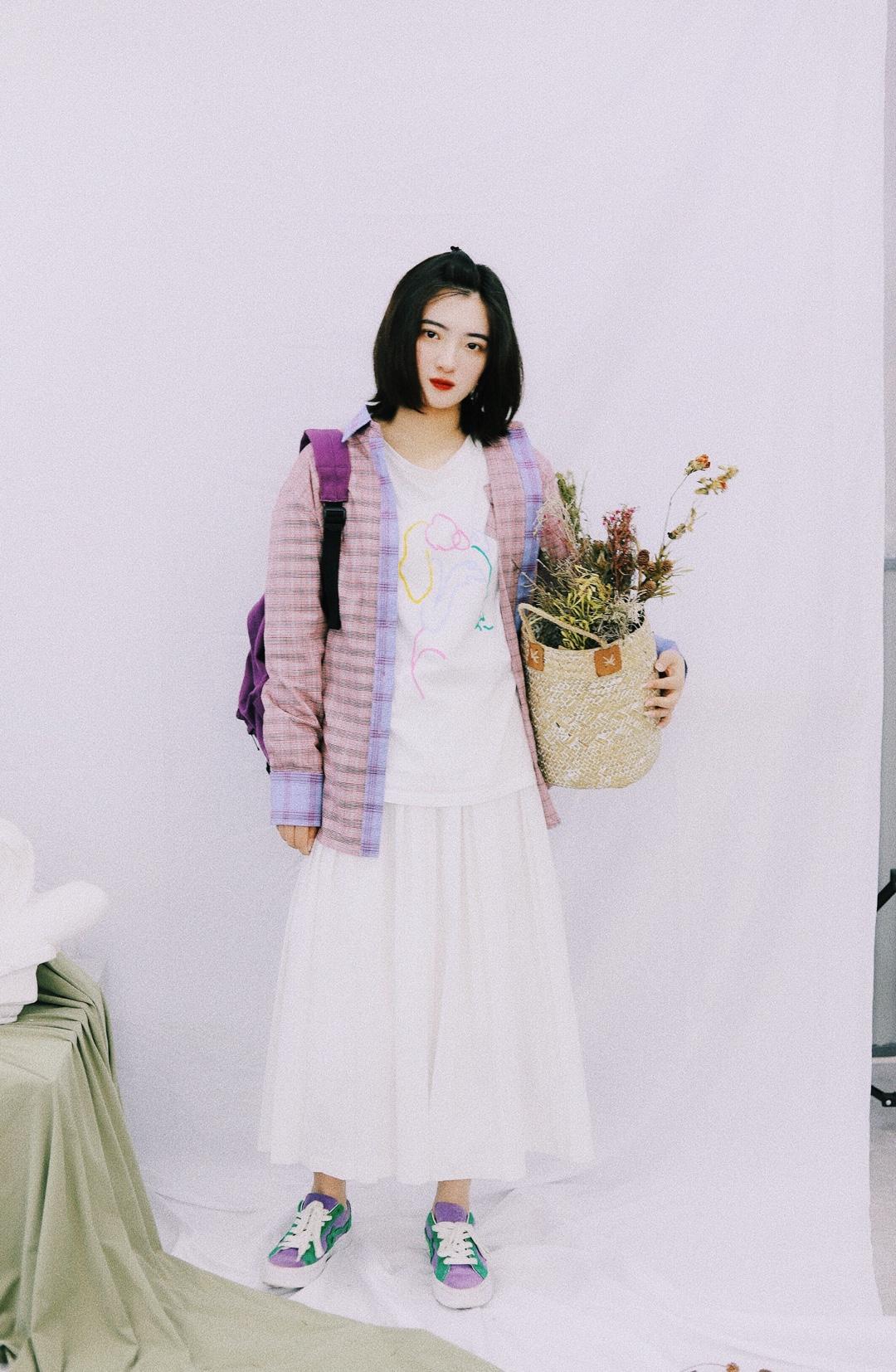 上身是一件白色短袖内搭 搭配一件紫色格子衬衫薄外套 下身是一条白色半身裙 搭配一双紫色帆布鞋 背上一个紫色的包包 这样一身就很适合初秋穿啦 #换季吸睛:薄外套上线#