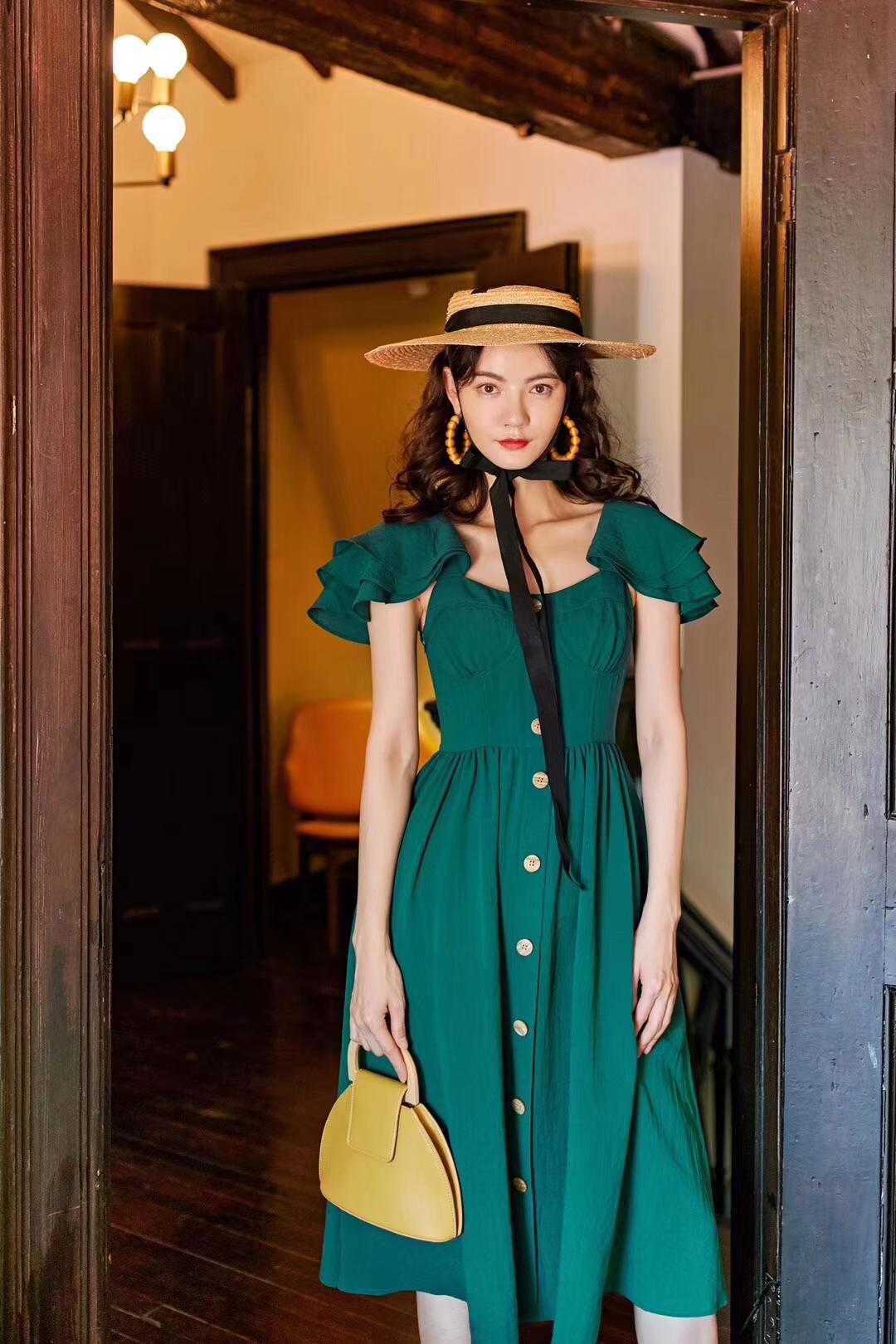 孔雀冠羽连衣裙。 孔雀一层一层的冠羽尤为吸引人,就像是这条连衣裙双肩处的点睛设计。不似往常的平薄风,双肩是面料的层层相叠,质感饱满,搭配浓烈的绿色,像极了美丽的孔雀。藏匿于双肩之下的是吊带款式的裙身,包裹双胸更加性感。白色纽扣的点缀,调合了整体偏厚重的色系。强垂坠的裙身,走动间气场全开。