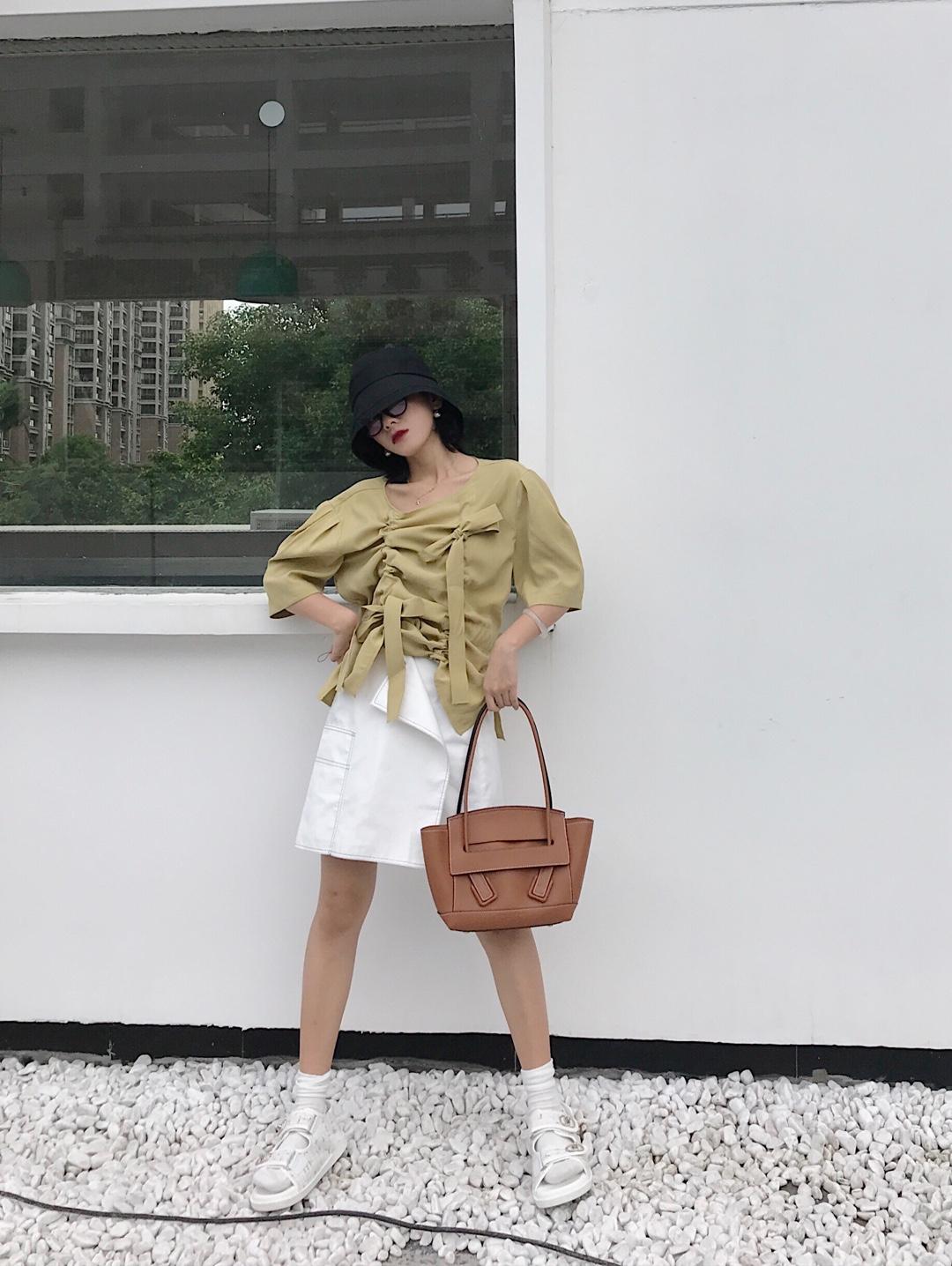 #夏装最后一波,我带你盘!# 不规则可以两穿的半身裙,白色也是百搭色,打破日常半身裙的调性! 上衣可抽褶打蝴蝶结!显得可爱又有个性,芥末绿显白一把手,搭配棕色的包包,今年流行的黑色帽子和镜框,很适合街拍凹造型!搭配整体感更强!