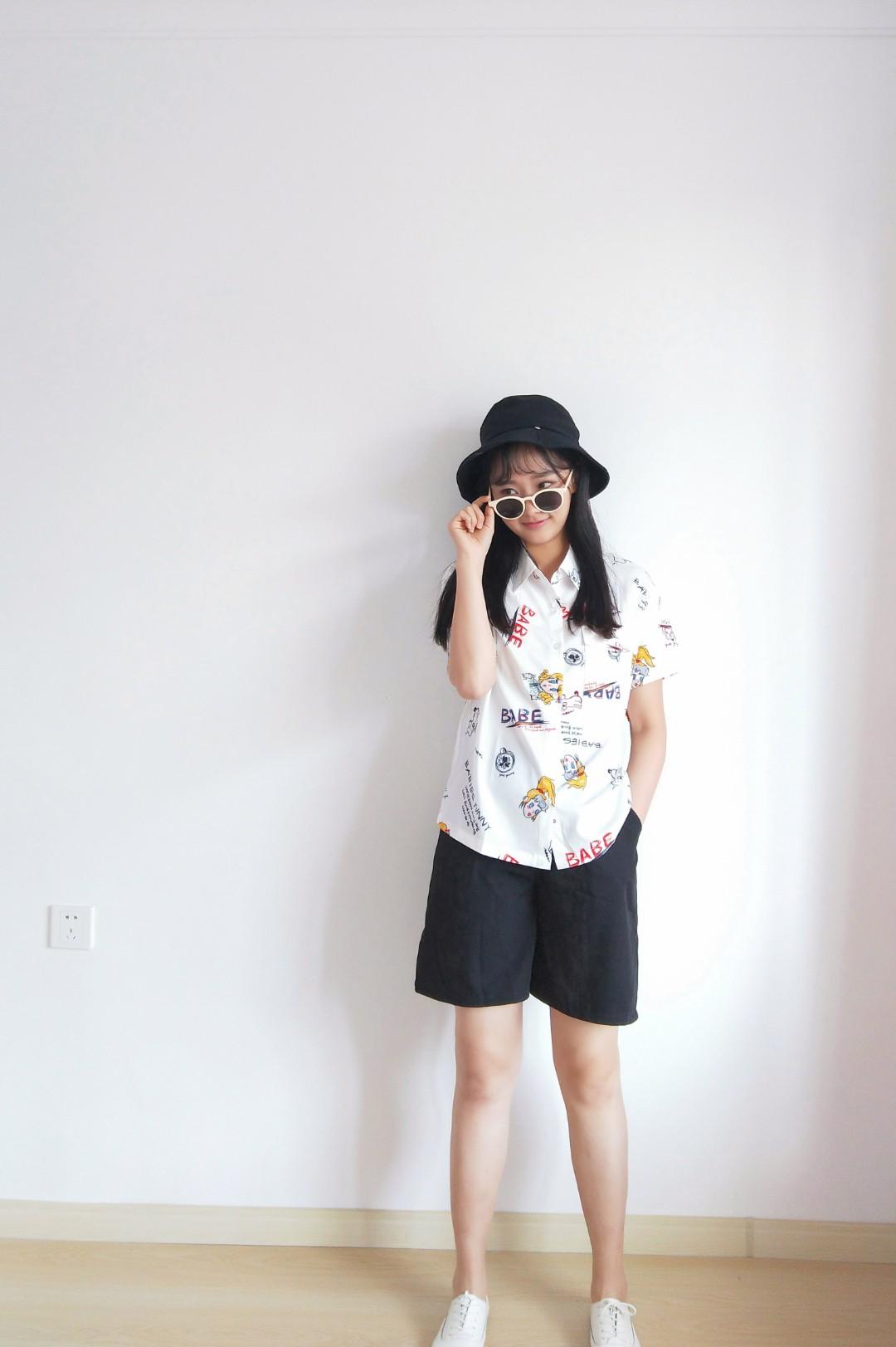 #不好惹女孩穿搭,A爆!#又是一套经典帅爆的黑白搭。上衣翻领衬衫,白底卡通字母图案,可爱又俏皮,短裤与帽子选择黑色,与上衣呈现反差对比,墨镜白边黑镜,符合这套穿搭主题,成为一道亮点。