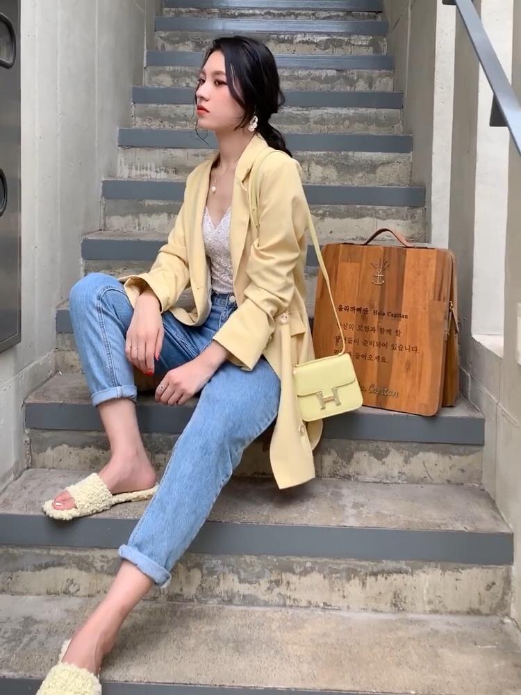 #入秋最靓!韩系小姐姐风# 这件薄款西装可以直接当西装连衣裙穿 非常的特别 比较女人 腰部腰带可以起到一个视觉上的收腰效果 也可以把它当成普通的西装穿 搭配蓝色牛仔裤搭配白T都非常好看 黄色的西装 我用黄色的包包和它做了一个撞色 因为这一套是比较休闲的look 所以搭配了一个黄色的毛毛拖鞋