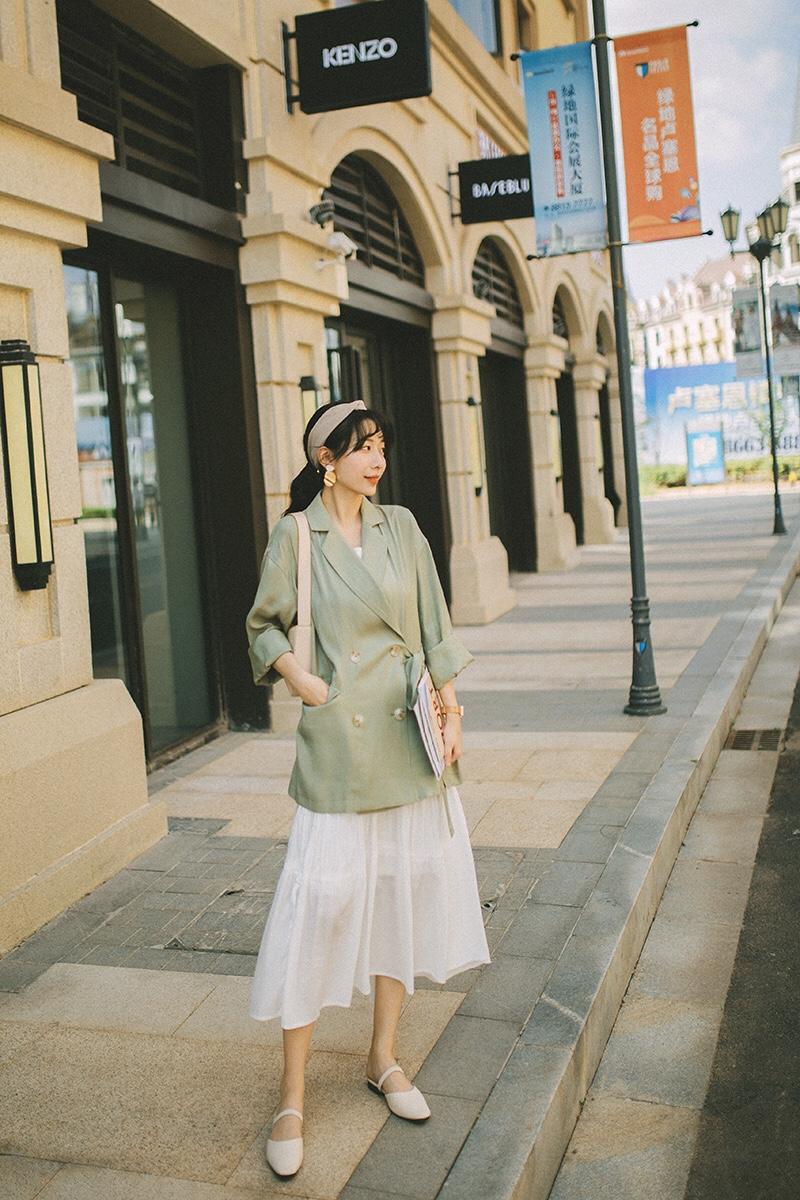 #粗腿女孩福音,遮肉穿它!# 博主158cm/43kg的梨型矮妹一只。 今日是复古港风的气质简约LOOK出街。 莫兰迪色系温柔又气质,丝光面料也是今年大热的元素。 这个长裙简直是梨型身材的我的福音,太好搭配太好穿了吧。很显瘦又遮肉。 虽然是西装外套,但是增加一些休闲原宿,比如发带和系带,增加慵懒休闲感哦。