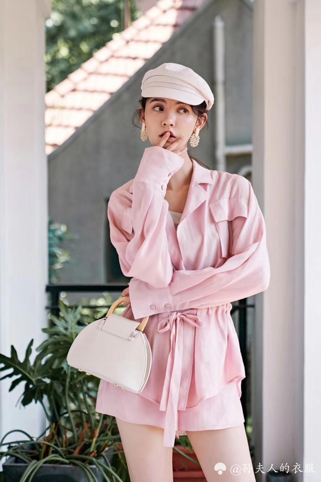 珊瑚粉套装 似纱似丝质的半透明面料,舒适清爽,早秋、春天穿刚刚好。保留了西装双翻的领子的样式,在腰间的运用抽绳设计,使层次感更强,更具时尚质感,让你化身成慵懒少女一枚。胸前对称口袋的装饰,穿着更具饱满感。下装则是高腰短裤,天丝面料的触感,亲肤更凉爽。粉色,中和了西装过于承重的感觉,多了跳跃的色彩,整个人活力四射起来。