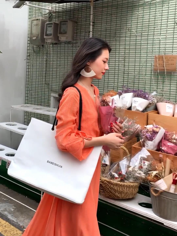 #秋装上新穿搭打卡# 秋天的季节也可以穿鲜艳的颜色! 橘色的V领连衣裙 非常的显白显瘦! 袖口蝴蝶结的设计非常少女! 搭配皮质大耳环和大包包 避免过于休闲 白色的包包和白色的耳环颜色上面呼应 整体在秋天还是非常亮眼的