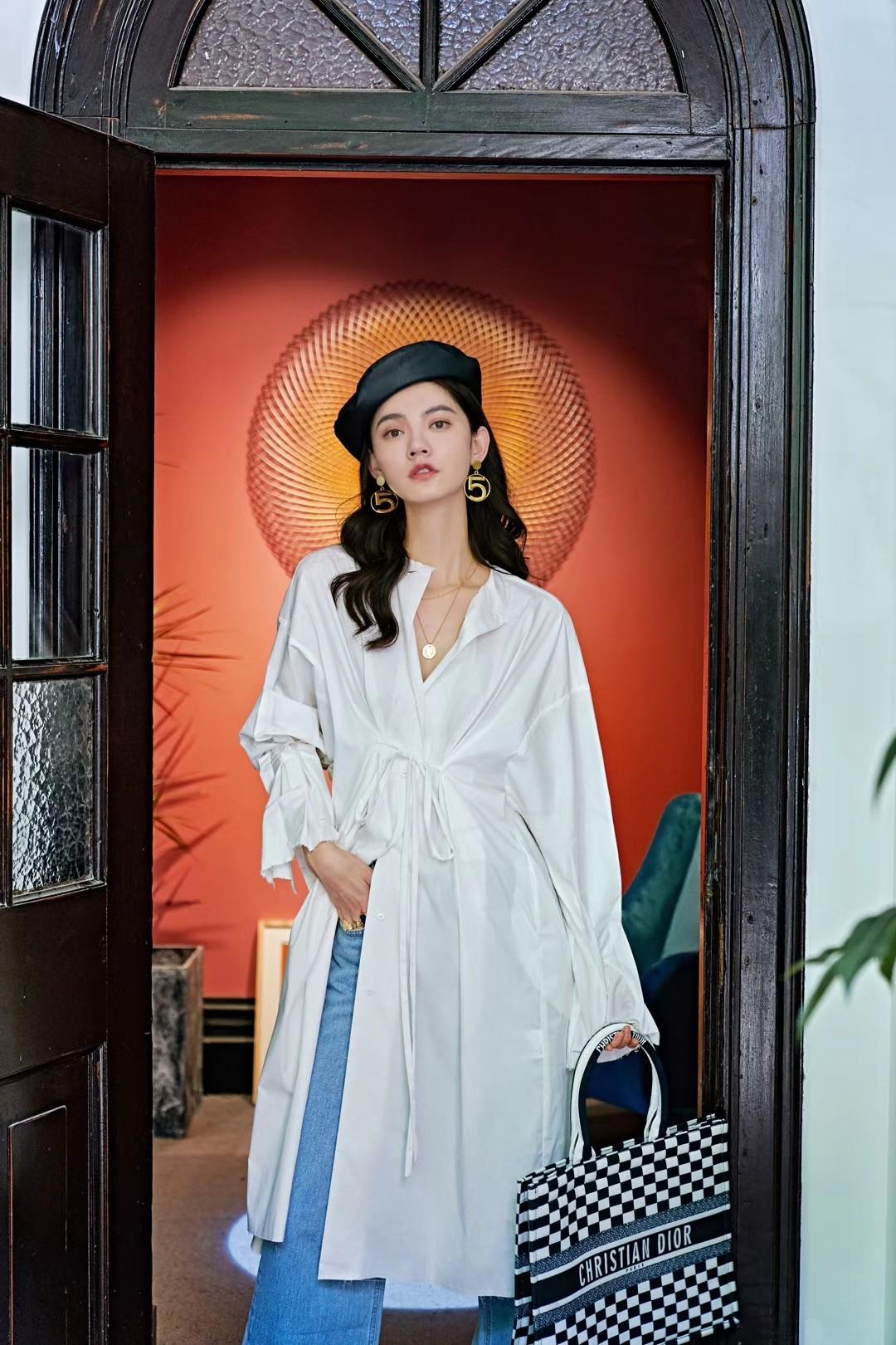 【VIMI】银月衬衫裙  白色的衬衣,有着一丝禁欲感。剔除了翻领,用不一的黄色纽扣纽合成圆领领口,线条感更加凸显。宽松的双袖融入了褶裥的设计,穿着舒适的同时保有纤细感。颇长的裙身,在腰间留有细长的带子,系上结勾勒出腰身,优越的身材比例立马展现。银白的色彩,光芒映衬之下,显露着隐隐约约的性感。 #秋装上新穿搭打卡#