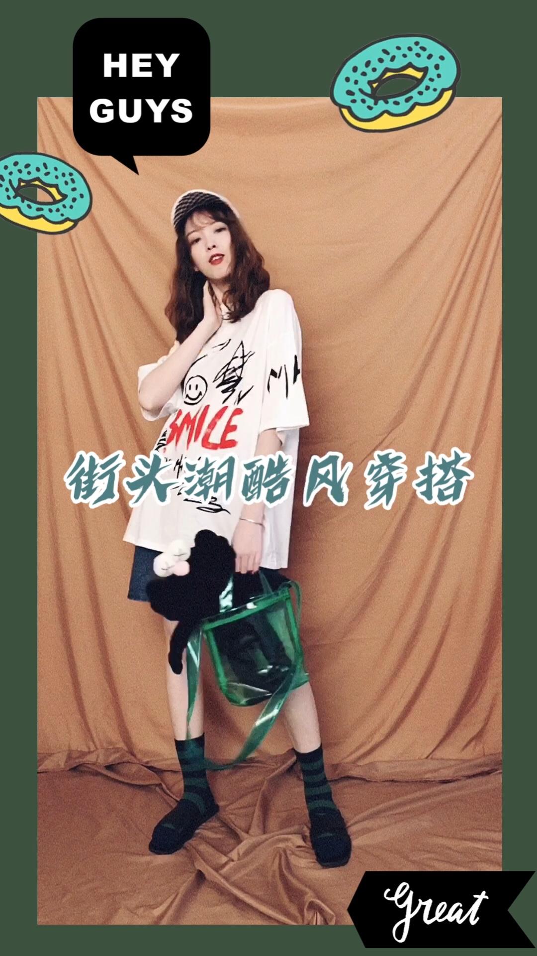 CC穿搭 这么简单的T恤牛仔裤穿搭,避免太过普通单调,大印花图案的T恤更为出众,长款宽松的版型十分舒适,下身搭配牛仔短裤,这样简单的搭配,需要其他配件去衬托,白色的鸭舌帽和衣服相呼应,黑色布娃娃装在绿色果冻包里十分可爱,绿黑条纹的长袜颜色上相呼应,这样的搭配十分独特可爱哟