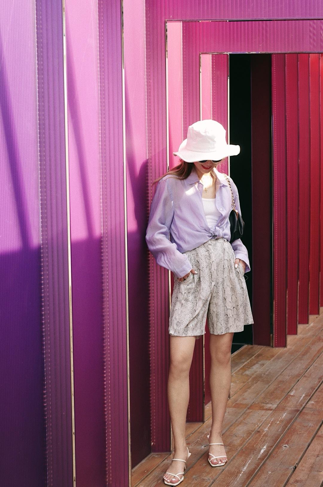 """百元搞定穿搭系列又来啦 今天这一身是我近期很爱的风格了 休闲+慵懒+酷+淡雅的时髦气质,四型合一! - 淡紫色的衬衫是我寻觅了很久的, 面料轻薄,既可以单穿,也可以扎在腰间当外套穿  内搭选择了一件白色的U领背心, Hm zara 几十块钱就能搞定的那种  裤子的话相比牛仔裤或者半裙, 搭配同样轻薄面料的中裤,似乎来的更加随性一些 裤子的蟒蛇纹图案有些演变,饱和度较低,与中裤的结合也还是非常时髦的~  因为中裤其实对小腿的要求还蛮高的 切记不能选圆头的笨拙的运动鞋(例如老爹鞋) 可以选择看上去""""轻""""一些的,秀气一点的, 细带的这种小高跟凉鞋就很适合 不宜选择色彩感强烈的,白色的就很符合整体性~ #小长假扎堆,脱单风速取!#"""
